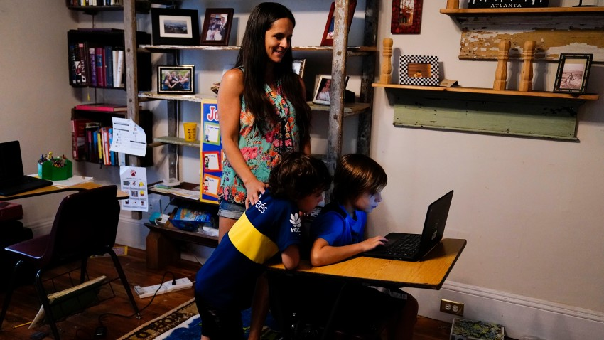 Anna Hamilton, 43, center, poses for a photograph with her sons, Henry, 6, left, and Adrian, 7, right, in their home
