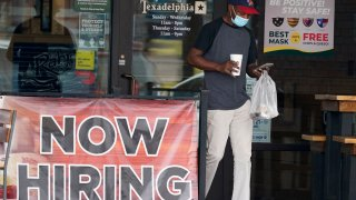 A customer wears a mask and looks at their cell phone as they carry their order past a now hiring sign at an eatery in Richardson, Texas, Wednesday, Sept. 2, 2020.