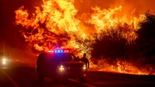 Flames lick above vehicles on Highway 162 as the Bear Fire burns in Oroville, Calif., on Wednesday, Sept. 9, 2020. The blaze, part of the lightning-sparked North Complex, expanded at a critical rate of spread as winds buffeted the region.