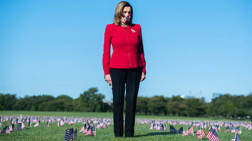 Speaker of the House Nancy Pelosi, D-Calif., stands amid flags planted on the National Mall as a memorial to the more than 200,000 Americans who have died due to the coronavirus, Sept. 22, 2020, in Washington, D.C.