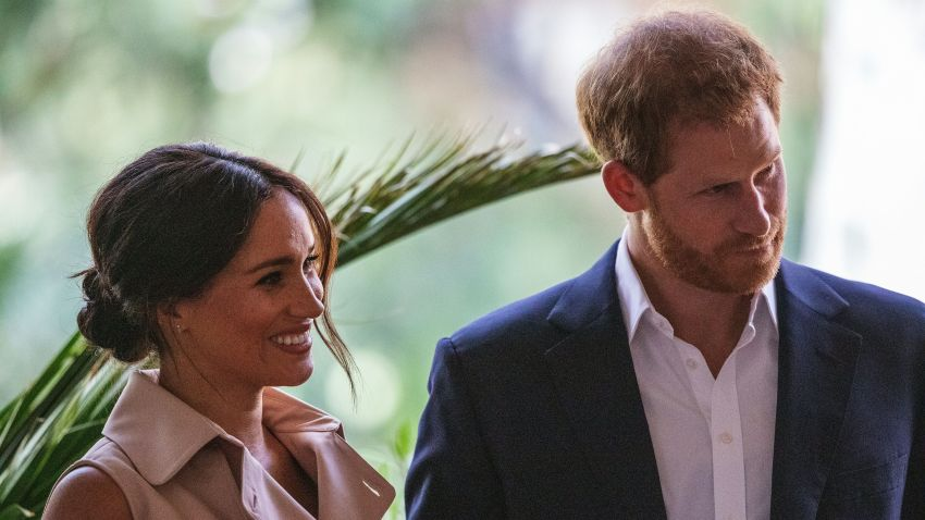 Britain's Prince Harry, Duke of Sussex(R) and Meghan, the Duchess of Sussex(L) stand on the stage at the British High Commissioner residency in Johannesburg where they will meet with Graca Machel, widow of former South African president Nelson Mandela, in Johannesburg, on October 2, 2019. - Prince Harry recalled the hounding of his late mother Diana to denounce media treatment of his wife Meghan Markle, as the couple launched legal action against a British tabloid for invasion of privacy.