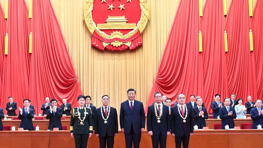 Chinese President Xi Jinping, also general secretary of the Communist Party of China Central Committee and chairman of the Central Military Commission, presents medals to the recipient of the Medal of the Republic.