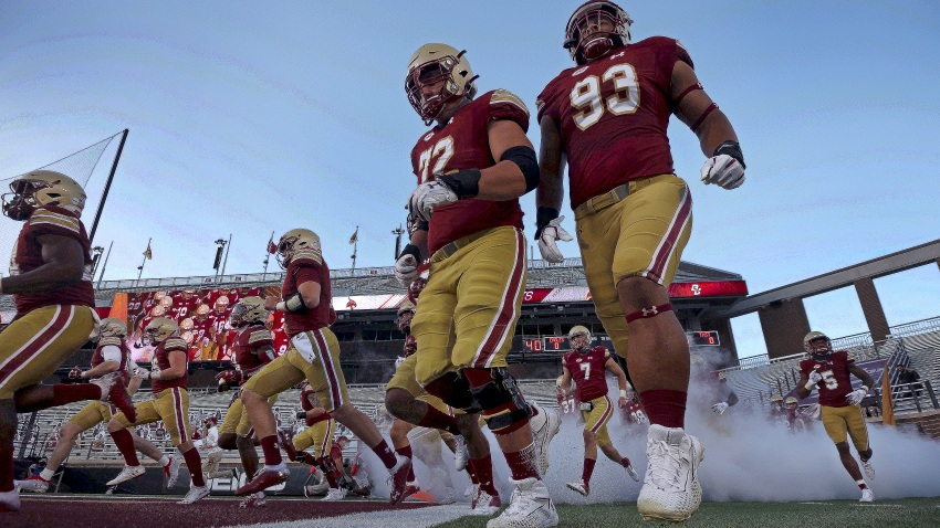 Boston College football players run onto the field at Alumni field