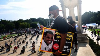 """Sean Greene, brother of Ronald Greene, listens to speakers and holds sign reading """"Justice for Ronald Greene"""" and """"Stop Police Brutality"""" at the Lincoln Memorial during the March on Washington on August 28, 2020, in Washington, DC."""