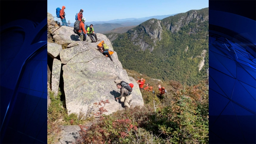 Rescue workers lift the body of a hiker who fell off a cliff in New Hampshire