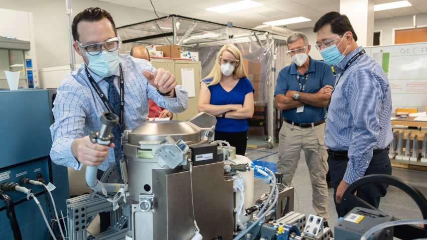 Astronaut Kate Rubins, center, and support personnel review the Universal Waste Management System, a low-gravity space toilet, in Houston