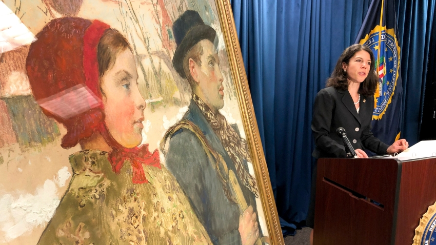 """Antoinette T. Bacon, speaks at a repatriation ceremony for the painting """"Winter"""" which is positioned to the left"""