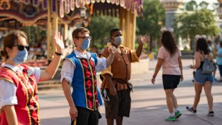In this July 11, 2020, file photo provided by Walt Disney World Resort, Disney cast members welcome guests to Magic Kingdom Park at Walt Disney World Resort in Lake Buena Vista, Florida.