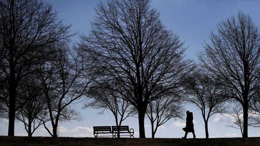 A woman walks near the shore at Boston's Castle Island