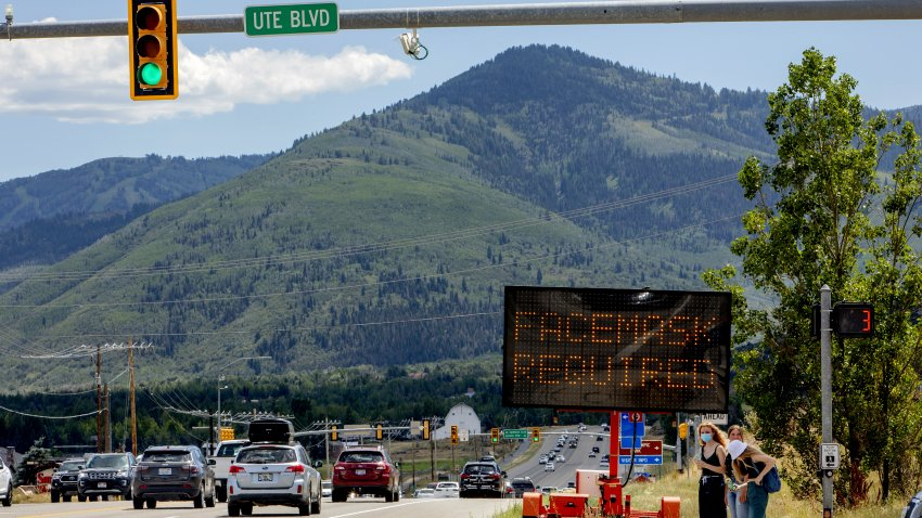 """Pedestrians walk in front of a street sign that reads """"Face Mask Requried"""" in Summit County near Park City, Utah"""