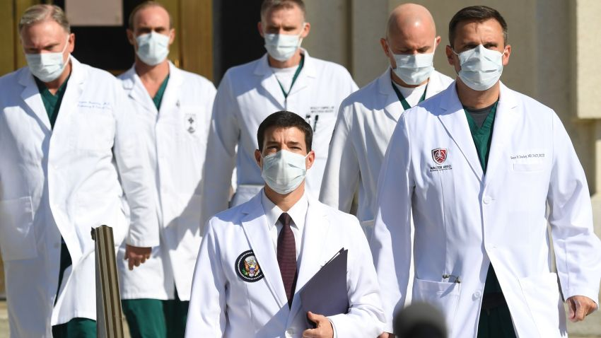 In this Oct. 5, 2020, file photo, White House physician Sean Conley (C) arrives to answer questions surrounded by other doctors, during an update on the condition of US President Donald Trump at Walter Reed Medical Center in Bethesda, Maryland.