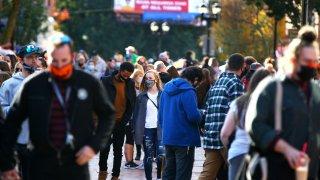 Crowds walk through a Salem, Mass., street wearing masks.