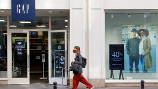 A woman wearing a protective face mask walks past a GAP store on October 22, 2020 in Paris, Franc