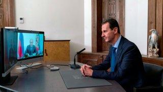 President Bashar Assad listens to Russian President Vladimir Putin