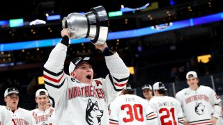 Zach Solow of the Northeastern Huskies celebrates with the winners trophy after defeating the Boston University Terriers in the 2020 Beanpot Tournament