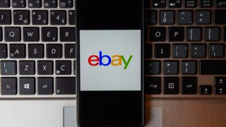 In this photo illustration an Ebay logo seen displayed on a smartphone with a laptop keyboard on the background.