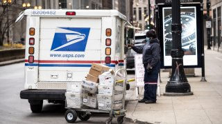 A United Postal Service (USPS) worker unloads packages in Chicago, Illinois, U.S., on Monday, Nov. 30, 2020. Online shoppers in the U.S. are expected to drop a record-busting $12.7 billion on Cyber Monday -- the busiest e-commerce day of the year -- presenting a valuable opportunity for retailers whose websites, customer service departments and delivery operations can withstand the period of crushing traffic.