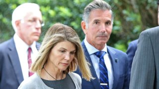 In this Aug. 27, 2019, file photo, actress Lori Loughlin and her husband Mossimo Giannulli leave Moakley Federal Courthouse after a brief hearing in Boston, Massachusetts.