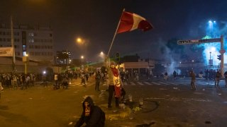 A protester holds a banner with the country's national color as police launch tear gas to disperse protesters who gathered at Plaza San Martin as part of a protest against newly appointed interim president Manuel Merino on November 14, 2020 in Lima, Peru.