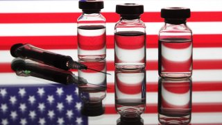 A medical syringe and vials in front of the U.S. flag