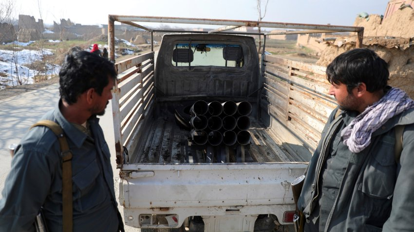 Afghan security personnel stand near a vehicle in which rockets were placed, in Bagram
