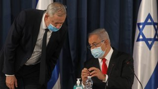"Israeli Prime Minister Benjamin Netanyahu (R) speaks with Alternate PM and Defence Minister Benny Gantz, both wearing protective mask due to the ongoing COVID-19 pandemic, during the weekly cabinet meeting in Jerusalem on June 7, 2020. - Netanyahu urged world powers to reimpose tough sanctions against Iran, vowing to curb Tehran's regional ""aggression"" hours after another deadly strike on pro-Iranian fighters in Syria. (Photo by Menahem KAHANA / AFP)"