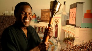 Former Olympic decathlete Rafer Johnson, 74, holds the same cauldron that he used to light the Olympic flame, located above the Los Angeles Memorial Coliseum, during the opening ceremony for the 1984 Olympic games in Los Angeles back on July 28, 2009. In background is a photograph that recorded that moment, located above dining room table of his home in Sherman Oaks on July 27, 2009.