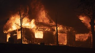 A house is seen burst into flames during the Zogg fire.