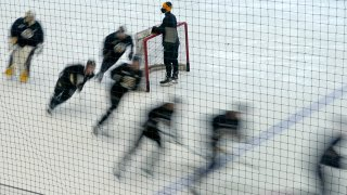 Boston Bruins players skate around a goal during a speed drill at the team's NHL hockey training camp, Monday, Jan. 4, 2021, in Boston.