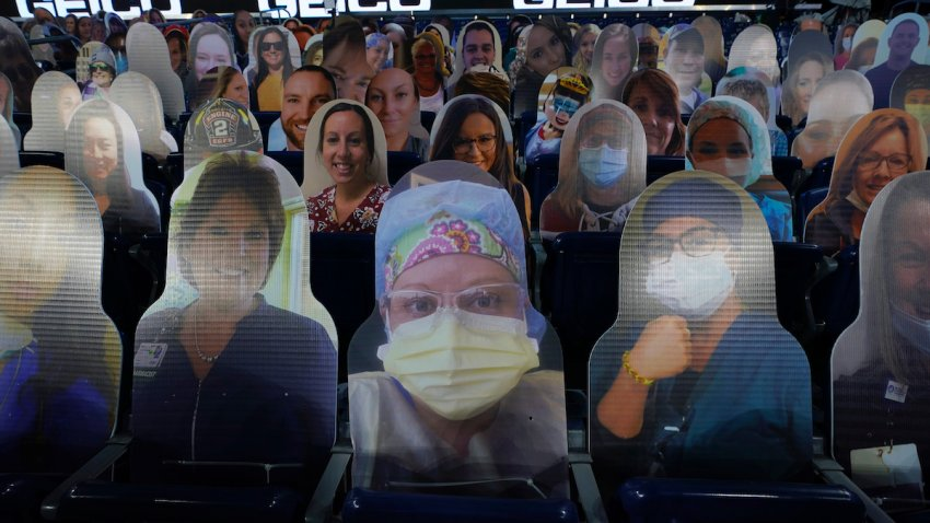 Cutout photos of people, including first responders and healthcare workers, sit in seats in Gillette Stadium