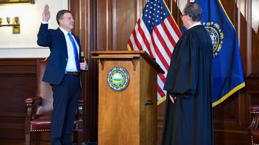 New Hampshire Gov. Chris Sununu holds his hand up as he is sworn in on Thursday, Jan. 7, 2021.