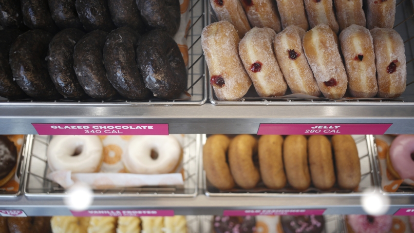 Doughnuts are displayed for sale inside a Dunkin' location