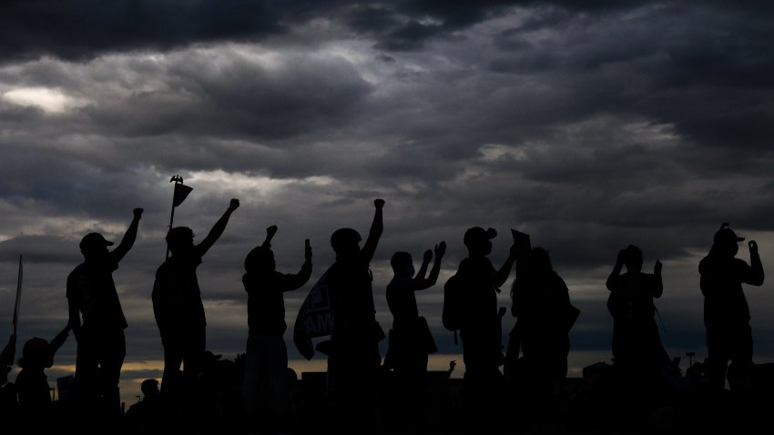 People hold their fists in the air as they shut down I-225 to protest the death of Elijah McClain on July 25, 2020 in Aurora, Colorado. On Friday, prosecutors said Aurora police officers who detained four Black girls by gunpoint after wrongly suspecting they were riding in a stolen car this summer won't be charged.