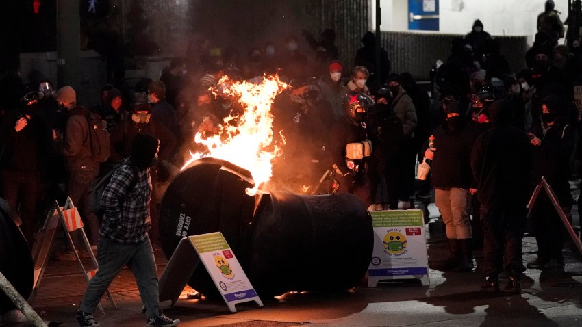 A trash can burns as people take part in a protest against police brutality, late Sunday, Jan. 24, 2021, in downtown Tacoma, Wash., south of Seattle. The protest came a day after at least two people were injured when a Tacoma Police officer responding to a report of a street race drove his car through a crowd of pedestrians that had gathered around him. Several people were knocked to the ground and at least one person was run over.