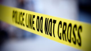 Yellow police line tape on a grayish background
