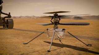 In this artist's concept, NASA's Ingenuity Mars Helicopter stands on the Red Planet's surface as NASA's Mars 2020 Perseverance rover (partially visible on the left) rolls away. Ingenuity made its first flight test on April 19, 2021.