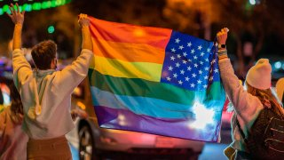 In this Nov. 7, 2020, file photo, people wave a rainbow flag as they celebrate the victory of Joe Biden in the 2020 presidential election in West Hollywood, California.