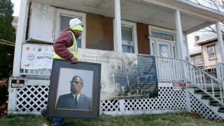 Rodnell P. Collins carries a painting of his uncle, Malcolm X