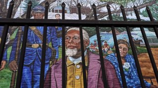 Past Amherst, Mass., area residents Henry Jackson, center, Lt. Frazar Stearns, left, and Anna Reed Goodwin, right, are featured on the Amherst Community History Mural, as seen through the adjacent West Cemetery fence, Friday, Jan. 15, 2021, in Amherst, Mass.