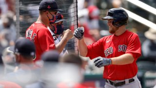 Christian Arroyo #39 of the Boston Red Sox high fives teammates after hitting a solo home run in a spring training game
