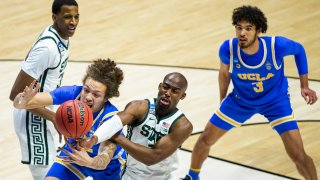 UCLA's Mac Etienne, front left, competes for a rebound with Michigan State's Joshua Langford during the second half of a First Four game in the NCAA men's college basketball tournament, Thursday, March 18, 2021, at Mackey Arena in West Lafayette, Indiana. UCLA won 86-80.