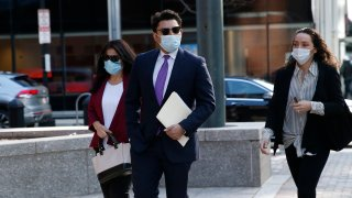 Former Fall River, Massachusetts, Mayor Jasiel Correia (center) arrives to the John Joseph Moakley United States Courthouse in Boston on Monday, April 26, 2021, when opening statements in Correia's federal corruption trial began.