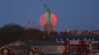 An almost full Pink Moon is seen in the sky behind the Statue of Liberty as the sun rises on April 26, 2021, in New York City. The Super Pink Moon will rise later in the day.