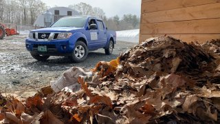 A pile of compost with a pickup truck in the background in Vermont.