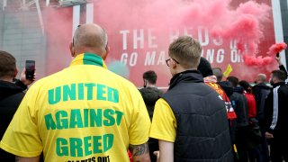 "A fan wears a shirt with a ""United Against Greed"" message, as fans gather to protest against the Glazer family, the owners of Manchester United, outside Old Trafford stadium"