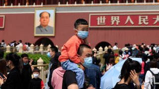 In this May 3, 2021, file photo, a man and child wearing masks visit Tiananmen Gate near the portrait of Mao Zedong in Beijing. China's ruling Communist Party is looking at allowing easing birth limits further to allow couples to have three children instead of two in response to the population's rising age, a state news agency said Monday, May 31, 2021.