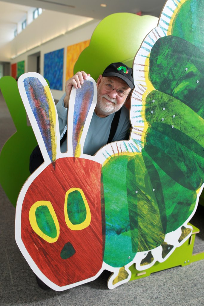 """This file photo shows Eric Carle stand with a large cutout of the iconic image from his children's book, """"The Very Hungry Caterpillar,"""" at his museum in Amherst, Mass."""