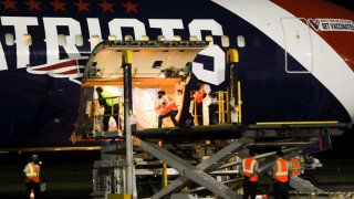 Workers unload coronavirus vaccines from the New England Patriots' plane in El Salvador on Wednesday, May 19, 2021.