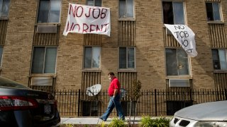"""FILE - In this May 20, 2020, file photo, signs that read """"No Job No Rent"""" hang from the windows of an apartment building during the coronavirus pandemic in Northwest Washington. The pandemic has shut housing courts and prompted authorities around the U.S. to initiate policies protecting renters from eviction. But not everyone is covered, and some landlords are turning to threats and harassment to force tenants out."""