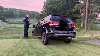 An officer observers an SUV stuck on the grass at Brae Burn Country Club in Newton